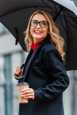 attractive and blonde woman in black coat smiling and holding paper cup