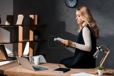 Photo pour Attractive and blonde businesswoman holding papers and sitting on table in office - image libre de droit