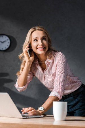attractive and blonde businesswoman in shirt smiling and talking on smartphone