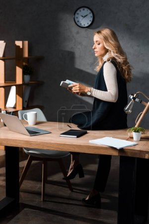 Photo for Attractive and blonde businesswoman holding papers and sitting on table in office - Royalty Free Image