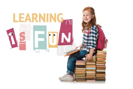 Photo pour Une élève joyeuse à tête rouge qui sourit en s'asseyant sur des livres près de l'apprentissage est une lettre amusante sur le blanc - image libre de droit