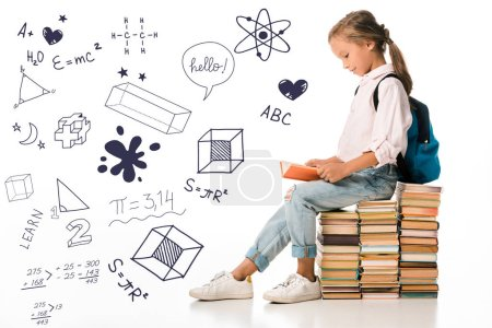 Photo for Cheerful schoolkid sitting on books and reading near letters and mathematical formulas  on white - Royalty Free Image