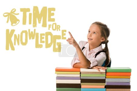 Photo for Positive schoolkid pointing with finger at time for knowledge letters near colorful books on white - Royalty Free Image