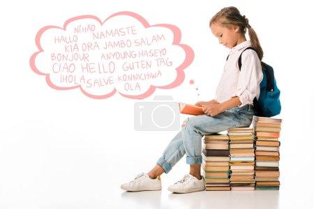 Photo pour Un écolier gai assis sur des livres et lisant près de lettres de vœux sur du blanc - image libre de droit