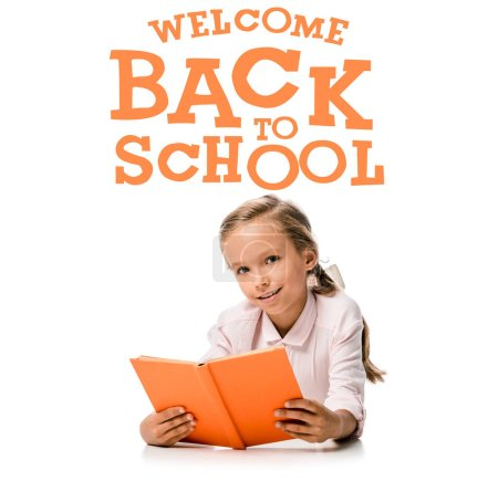 happy schoolkid holding orange book and smiling near welcome back to school letters on white