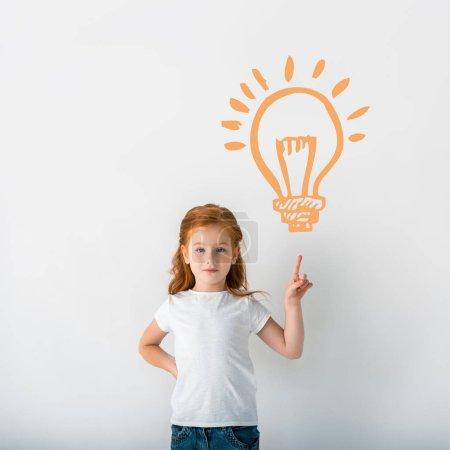 Photo pour Mignon rousse enfant regardant caméra et pointant avec doigt près de l'ampoule orange sur blanc - image libre de droit