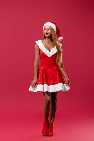 Photo for Attractive african american girl in christmas dress and santa hat looking away on red background - Royalty Free Image
