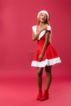 Photo pour Sexy africaine américaine en santa chapeau et robe de Noël épaule audacieuse sur fond rouge - image libre de droit