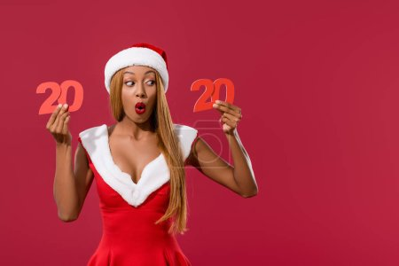 Photo for Surprised african american girl in santa hat and christmas dress holding 2020 paper cut number isolated on red - Royalty Free Image