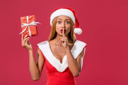 Photo pour Jolie Africaine d'Amérique en santa chapeau et robe de Noël tenant boîte cadeau et montrant signe de brousse isolée sur rouge - image libre de droit