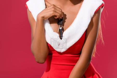 Photo for Partial view of sexy african american in christmas dress holding car keys near chest isolated on red - Royalty Free Image