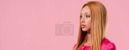 Photo pour Photo panoramique d'une Américaine africaine blonde et stylisée regardant loin, isolée sur le concept de poupée rose, mode - image libre de droit