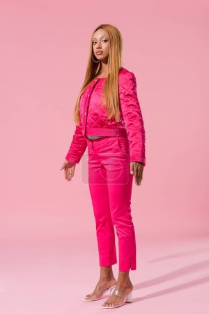 Photo pour Attractive, trendy african american woman standing on pink background, fashion doll concept - image libre de droit