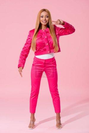 Photo pour Une Africaine d'Amérique souriante et branchée montrant un geste de victoire sur fond rose, concept de poupée mode - image libre de droit