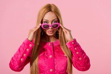 Photo pour Femme afro-américaine élégante touchant des lunettes de soleil et regardant la caméra isolée sur le concept de poupée rose, mode - image libre de droit