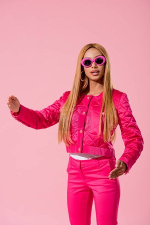 Photo for Stylish african american woman in sunglasses looking at camera isolated on pink, fashion doll concept - Royalty Free Image