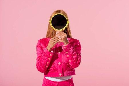 Photo pour Une Africaine d'Amérique à la mode se cache derrière un miroir isolé sur un concept de poupée de mode rose - image libre de droit