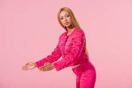 Photo pour Jolie Africaine d'origine américaine pointant du doigt avec les mains isolées sur une poupée rose, concept mode - image libre de droit