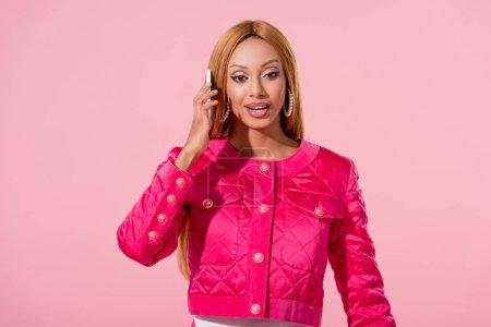 Photo pour Souriante, élégante femme afro-américaine parlant sur smartphone isolé sur rose, concept de poupée de mode - image libre de droit