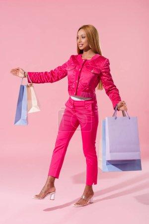 Photo pour Souriant, femme afro-américaine à la mode tenant des sacs à provisions sur fond rose, concept de poupée de mode - image libre de droit