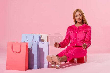 Photo for Smiling, trendy african american woman sitting on gift box near shopping bags on pink background, fashion doll concept - Royalty Free Image