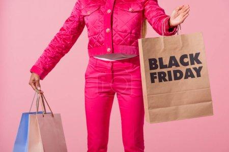 Photo pour Vue partielle de femme afro-américaine stylée tenant un sac à provisions avec inscription du vendredi noir sur fond rose, concept de poupée de mode - image libre de droit