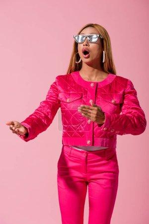 Photo pour Chic, choquée femme africaine américaine regardant loin isolée sur le concept de poupée rose, mode - image libre de droit