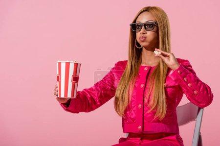 Photo pour Stylsh afro-américaine assise sur une chaise et mangeant du pop-corn isolé sur rose, concept de poupée de mode - image libre de droit