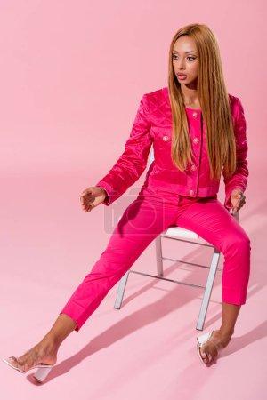 Photo pour Mode africaine américaine assise sur une chaise à l'arrière-plan rose, concept de poupée mode - image libre de droit