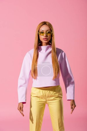 Photo pour Front view of stylish, blonde african american woman standing isolated on pink, fashion doll concept - image libre de droit