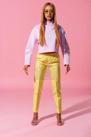 Photo pour Vue pleine longueur de élégant, blonde afro-américaine femme debout sur fond rose, concept de poupée de mode - image libre de droit