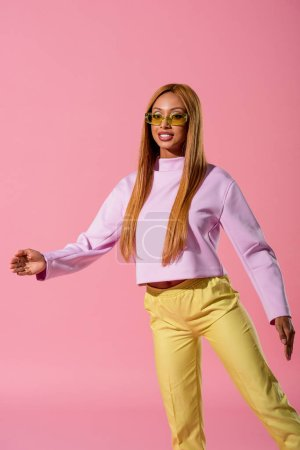 Photo pour Trendy, blonde african american woman stepping isolated on pink, fashion doll concept - image libre de droit