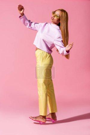 Photo pour Élégante femme afro-américaine debout sur fond rose, concept de poupée de mode - image libre de droit