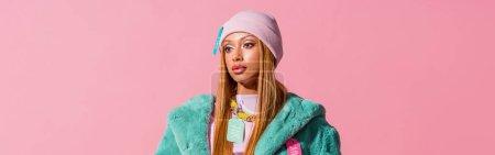 Photo pour Photo panoramique d'une Africaine d'Amérique réfléchie et élégante portant des étiquettes sur ses vêtements, isolée sur un concept de poupée de mode rose - image libre de droit