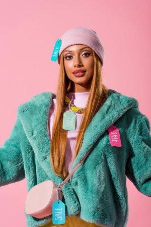 Photo pour Élégante femme afro-américaine avec des étiquettes de vente sur les vêtements en regardant la caméra isolée sur rose, concept de poupée de mode - image libre de droit