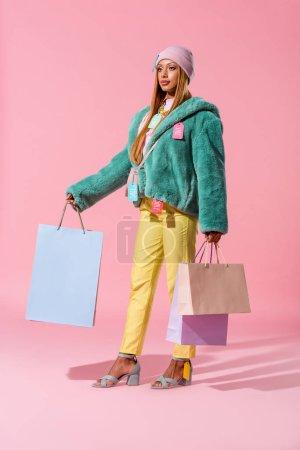 Foto de Hermosa y elegante mujer africaica americana que tiene bolsas de la compra en el fondo rosa, concepto de muñeca de moda. - Imagen libre de derechos