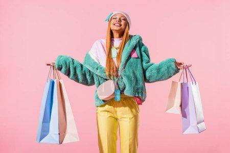 Photo pour Heureuse, élégante femme afro-américaine debout avec les yeux fermés et tenant des sacs à provisions isolés sur rose, concept de poupée de mode - image libre de droit