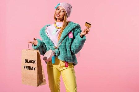 Foto de Jovencita africana alegre y de moda que tiene tarjeta de crédito y bolsa de compras con inscripción en negro el viernes aislado en el concepto rosa de muñeca de moda. - Imagen libre de derechos