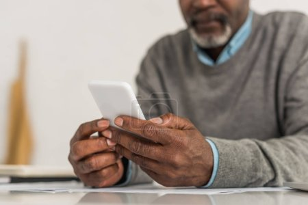 Photo pour Vue recadrée d'un homme afro-américain âgé utilisant un smartphone assis à table - image libre de droit