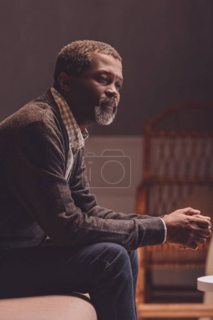 Photo for Lonely, senior african american man looking away while sitting on sofa - Royalty Free Image