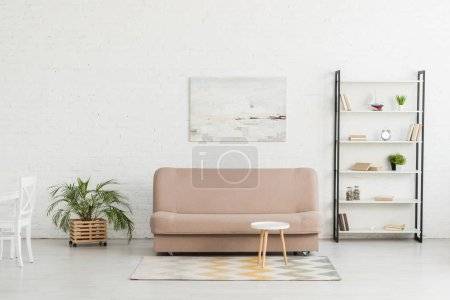 Photo for Spacious living room with white wall, sofa, rack with books, round table and potted plants - Royalty Free Image