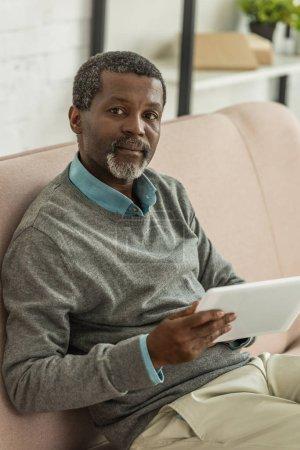 Photo pour Homme afro-américain grave tenant tablette numérique et regardant la caméra - image libre de droit