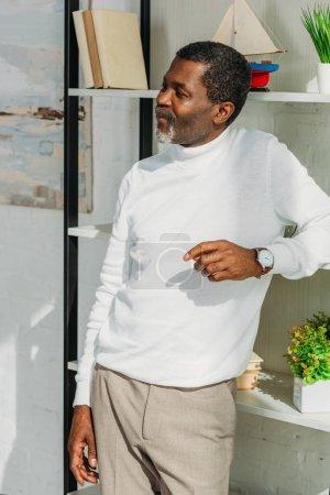 Photo pour Homme afro-américain positif dans une tenue élégante debout près de rack et regardant loin - image libre de droit