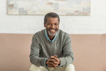 Photo pour Senior homme afro-américain assis sur le canapé avec les mains serrées et souriant à la caméra - image libre de droit