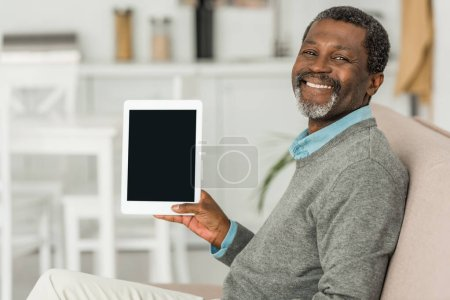 cheerful african american man holding digital tablet with blank screen and smiling at camera