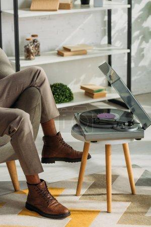 Photo pour Crochet vue d'un Africain américain assis dans un fauteuil et écoutant de la musique sur un tourne-disque - image libre de droit