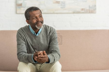Photo for Smiling african american man sitting on sofa and looking away - Royalty Free Image