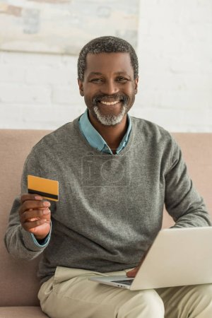 senior african american man sitting on sofa with laptop, holding credit card and smiling at camera
