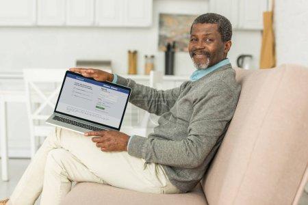 kyiv, ukraine - 2. Oktober 2019: fröhlicher afrikanisch-amerikanischer Mann sitzt auf Sofa und zeigt Laptop mit Facebook-App auf dem Bildschirm.