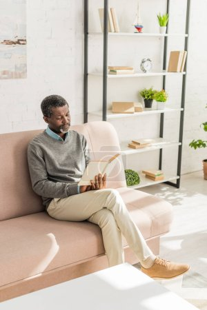Photo for Senior african american man sitting on sofa in living room and reading book - Royalty Free Image